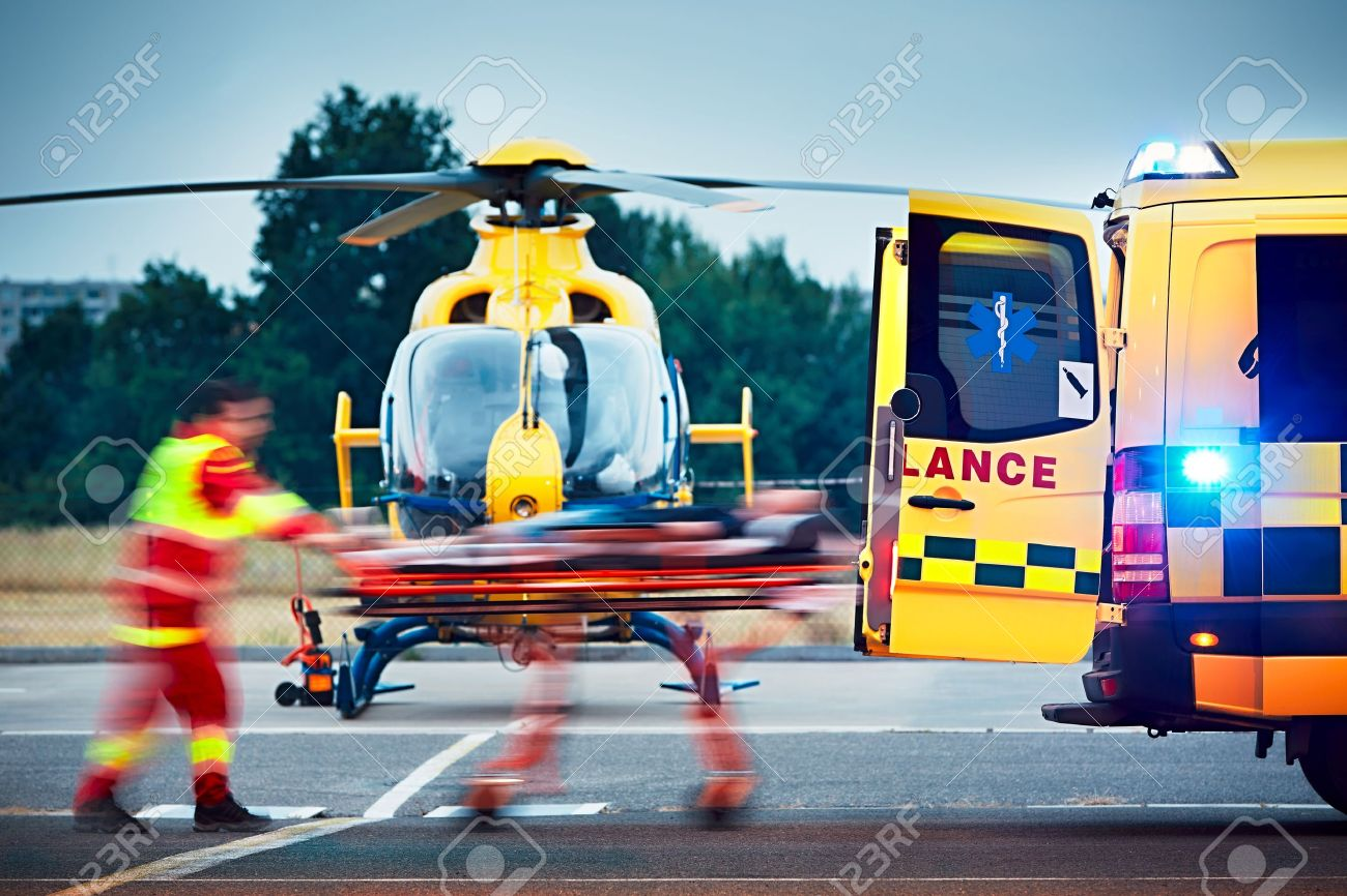 Cooperation between air rescue service and emergency medical service on the ground. Paramedic is pulling stretcher with patient to the ambulance car. Standard-Bild - 60418016