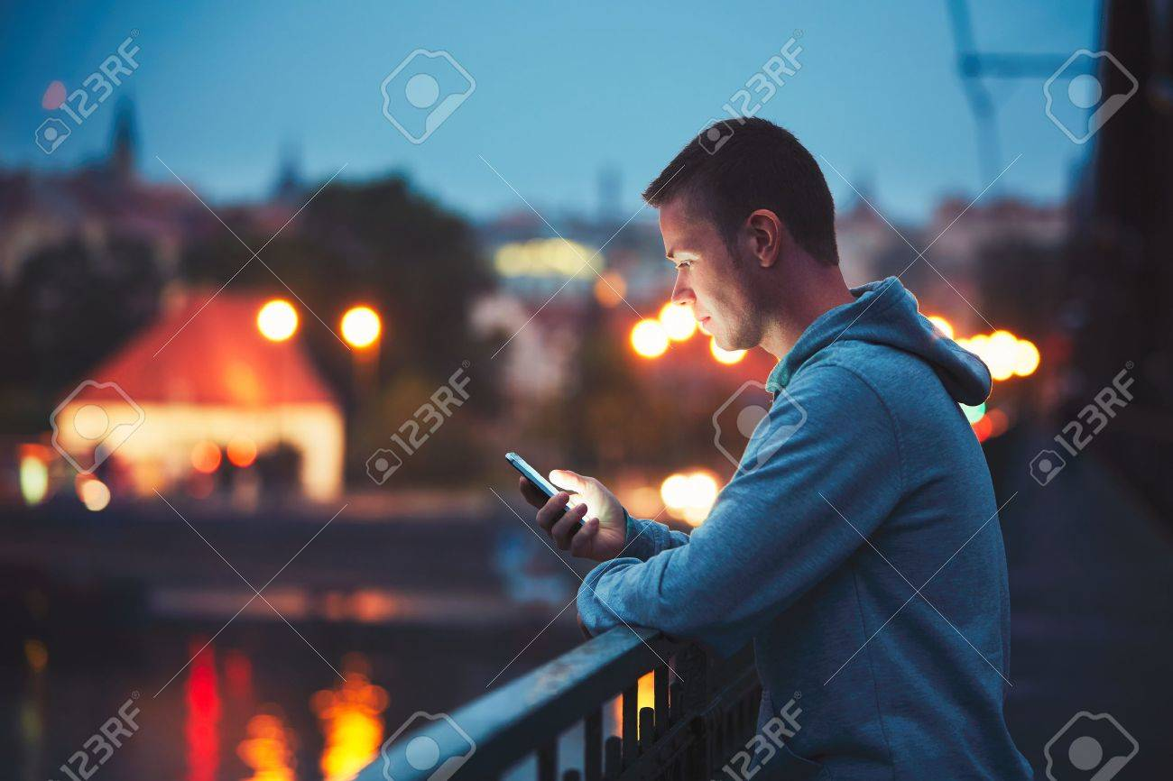 Alone in the night city with mobile phone. Handsome dreamy man reading message (or looking on the video) on his smartphone. Standard-Bild - 61268144