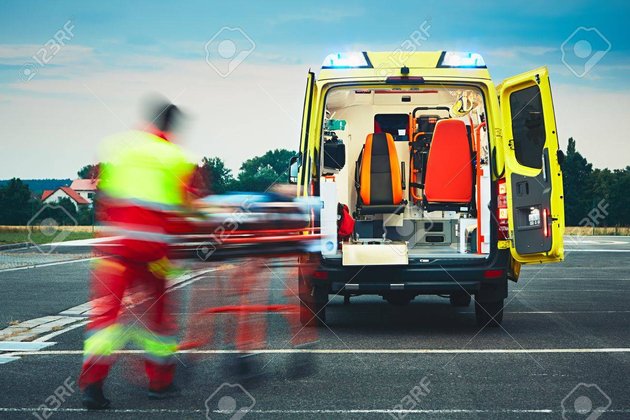 Emergency medical service. Paramedic is pulling stretcher with patient to the ambulance car. Standard-Bild - 65695568