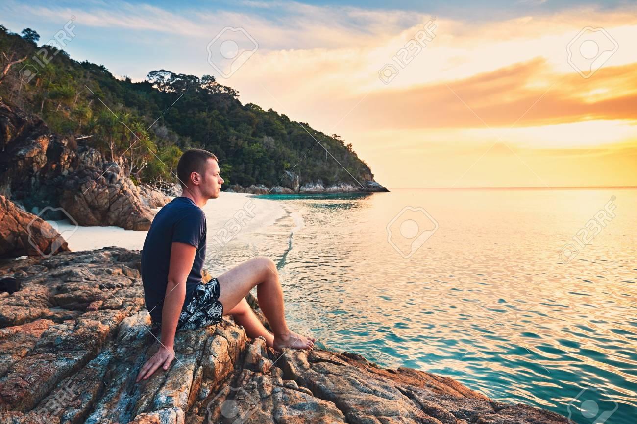 Le REPOS et les VACANCES vont de pair avec notre foi chrétienne... 76737818-contemplation-at-the-sunset-alone-young-man-on-the-beautiful-sand-beach-