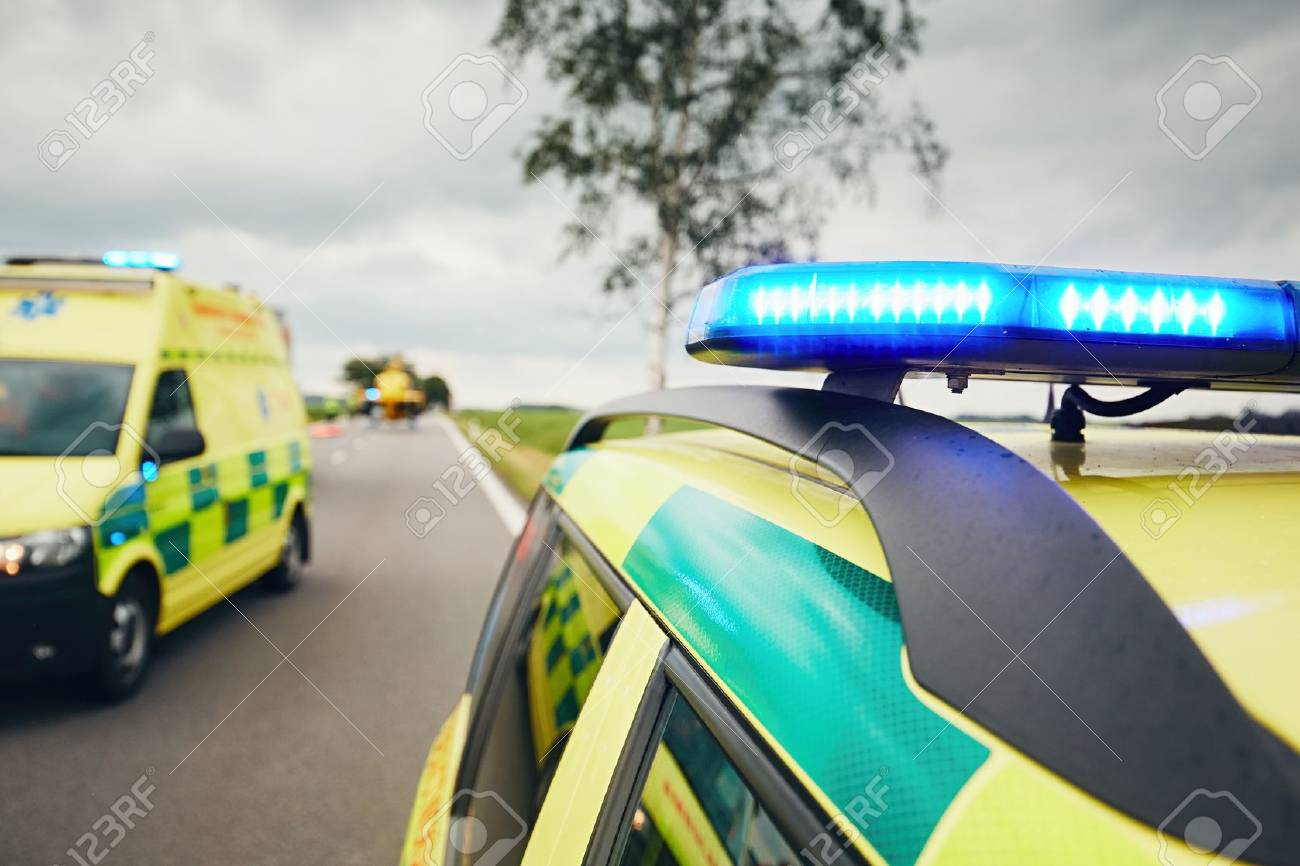 Ambulance cars. Teams of the Emergency medical service are responding to an traffic accidnet in bad weather. - 80864292