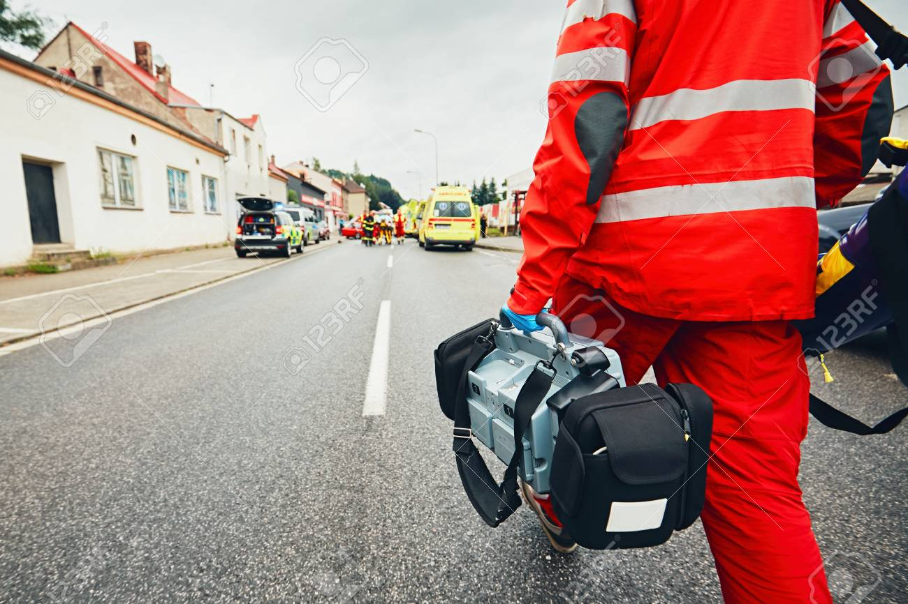 Hand of the doctor with defibrillator. Teams of the Emergency medical service are responding to an traffic accident. - 80887948