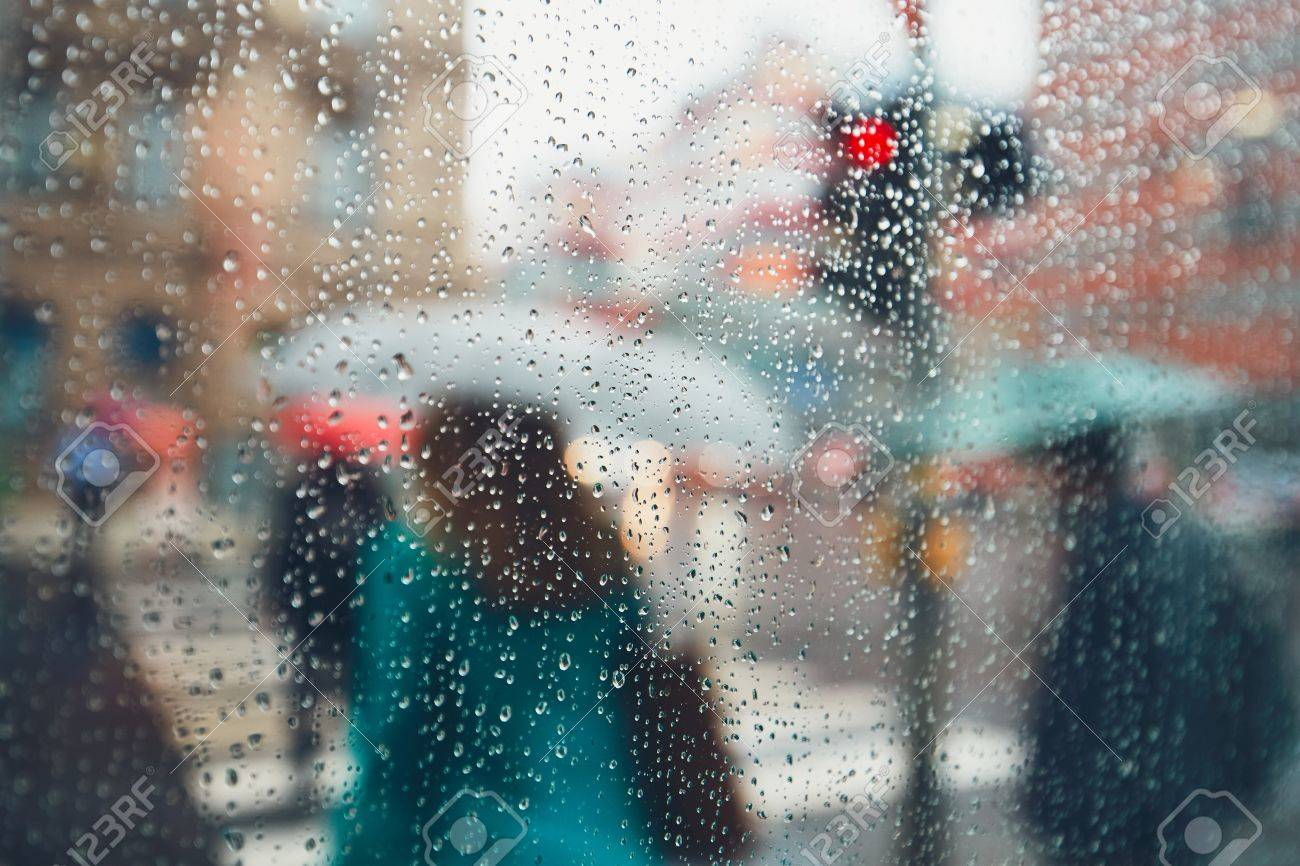 Gloomy day in the city. People in heavy rain. Selective focus on the raindrops. Prague, Czech Republic. - 81265975