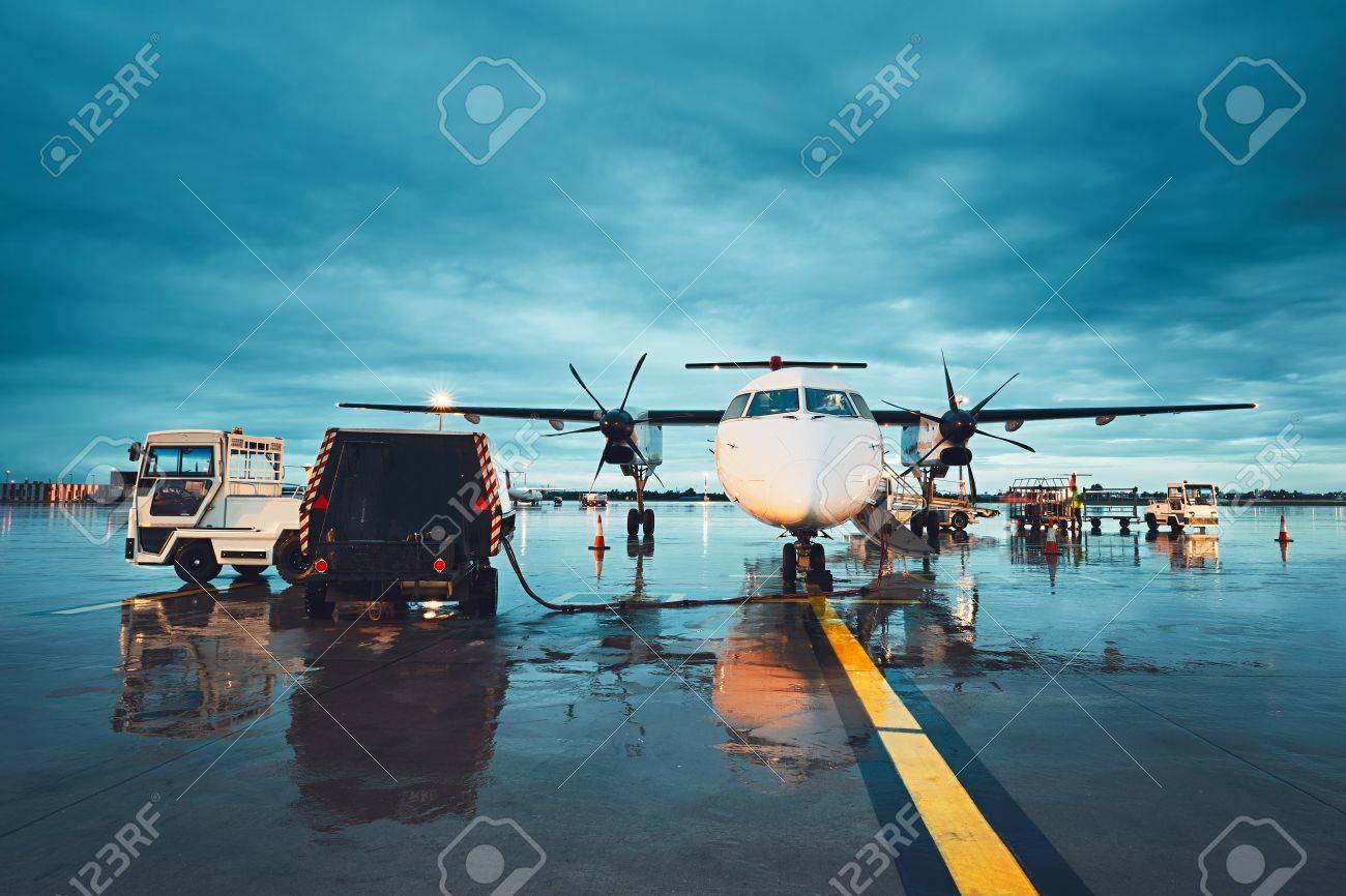 A busy airport in the rain. Preparation of the propeller airplane before flight. - 83227709
