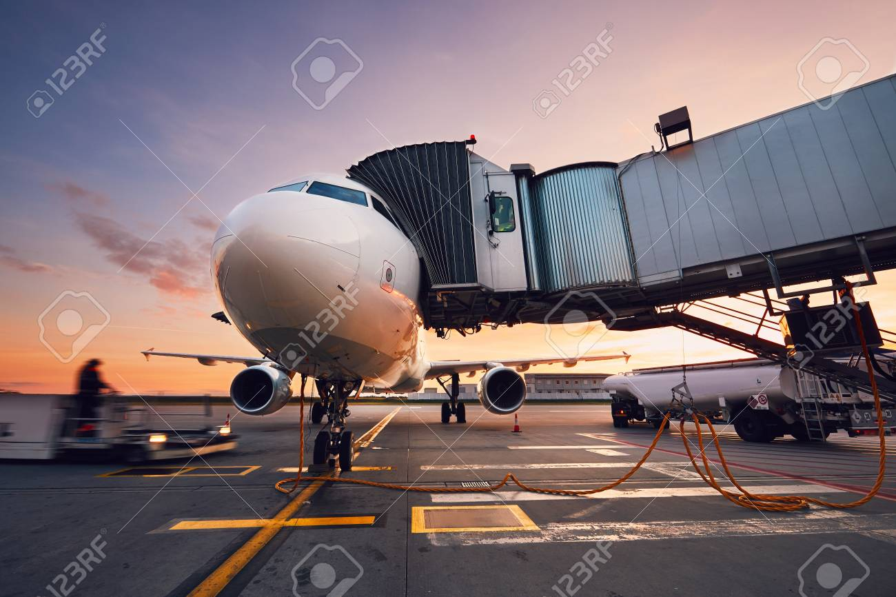 Busy airport at the colorful sunset. Preparation of the airplane before flight. - 88995484