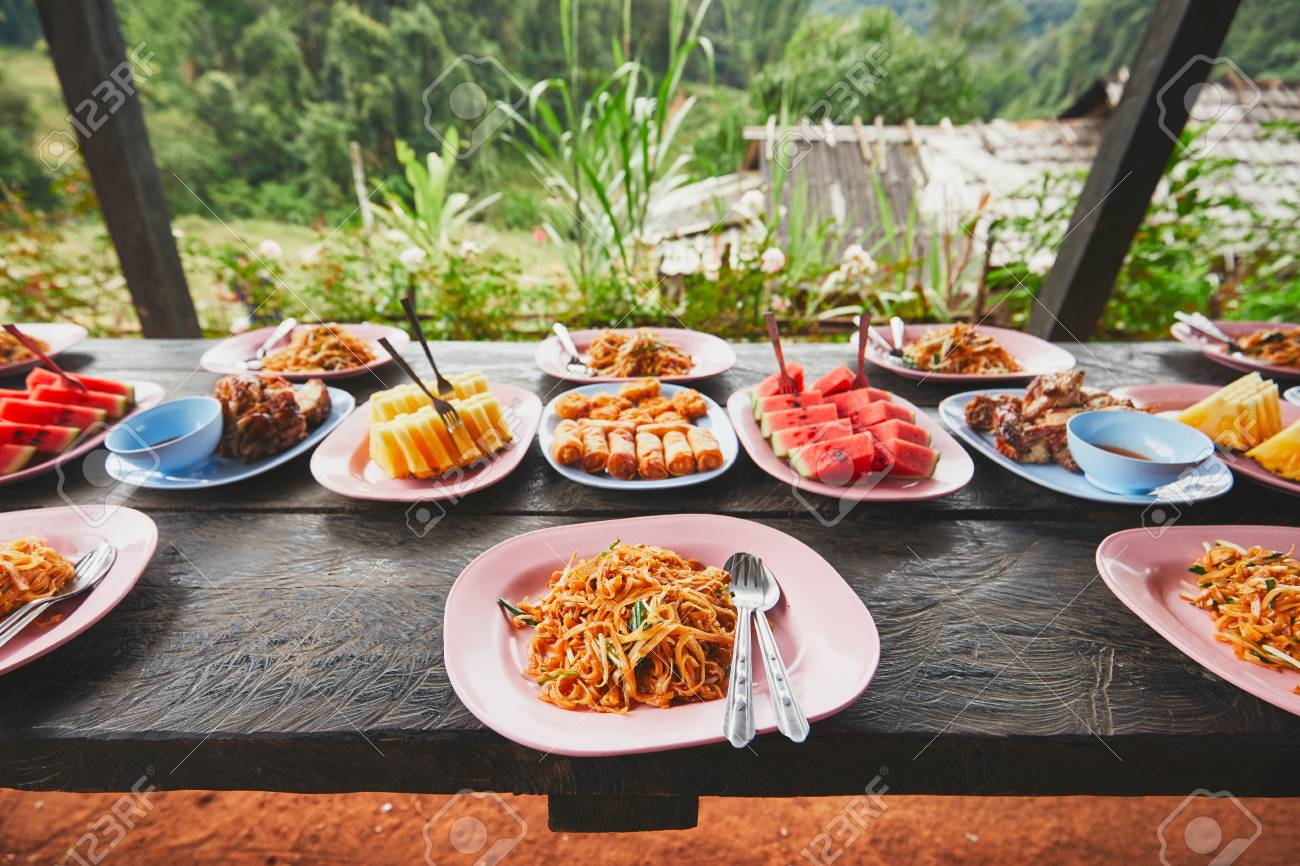 Lunch in the middle of the jungle. The table full of foods and fruits. Traditioal Pad Thai, spring rolls, melon and pineapple. Chiang Mai Province, Thailand. - 91700652