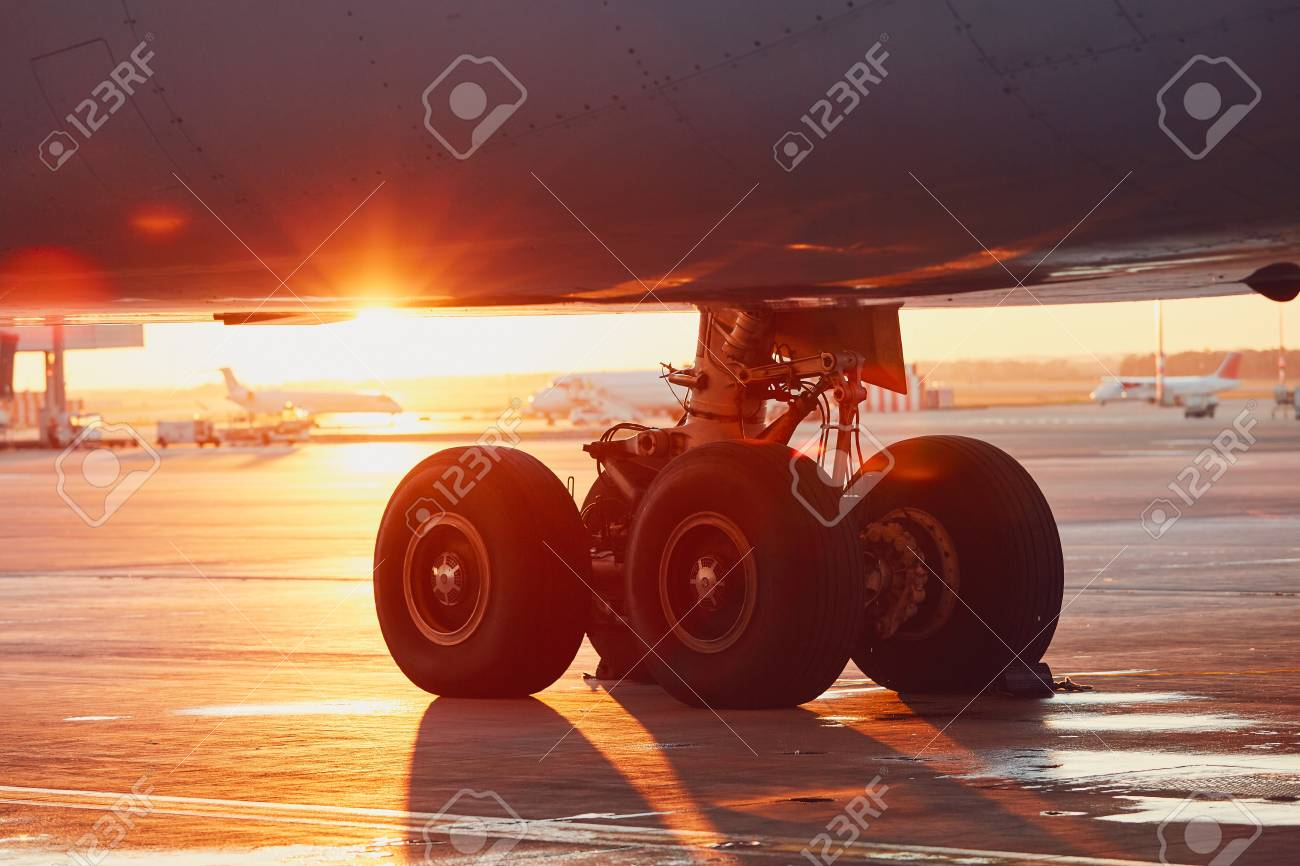 Landing gear of the airplane. Amazing sunset at the airport. - 92187784
