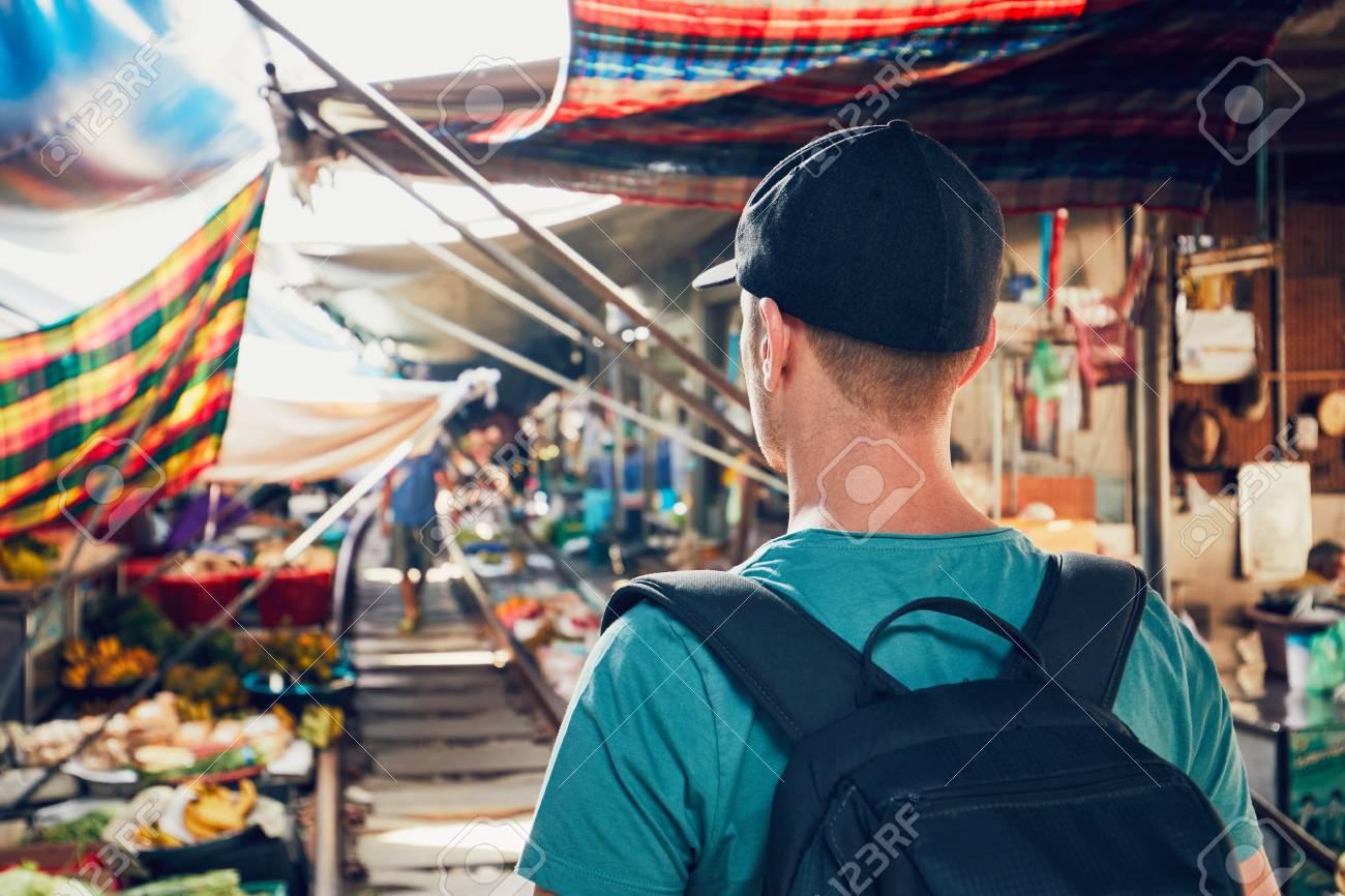 Young man (tourist) walking to open market along the railroad track. Maeklong railway market close to Bangkok in Thailand. - 92879939