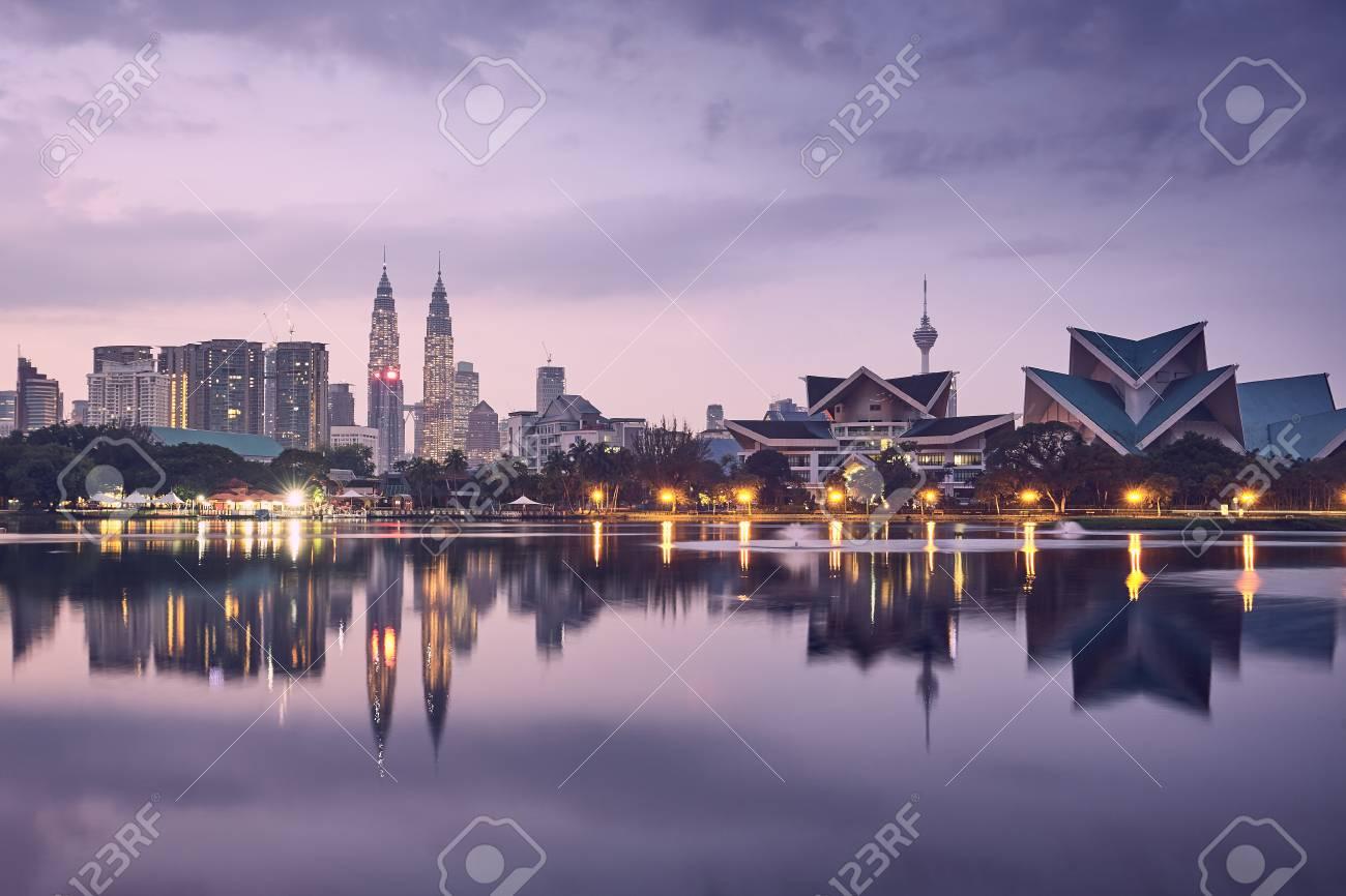 Moody sunrise in Kuala Lumpur in Malaysia. Reflection of the urban skyline in the lake. - 104683394