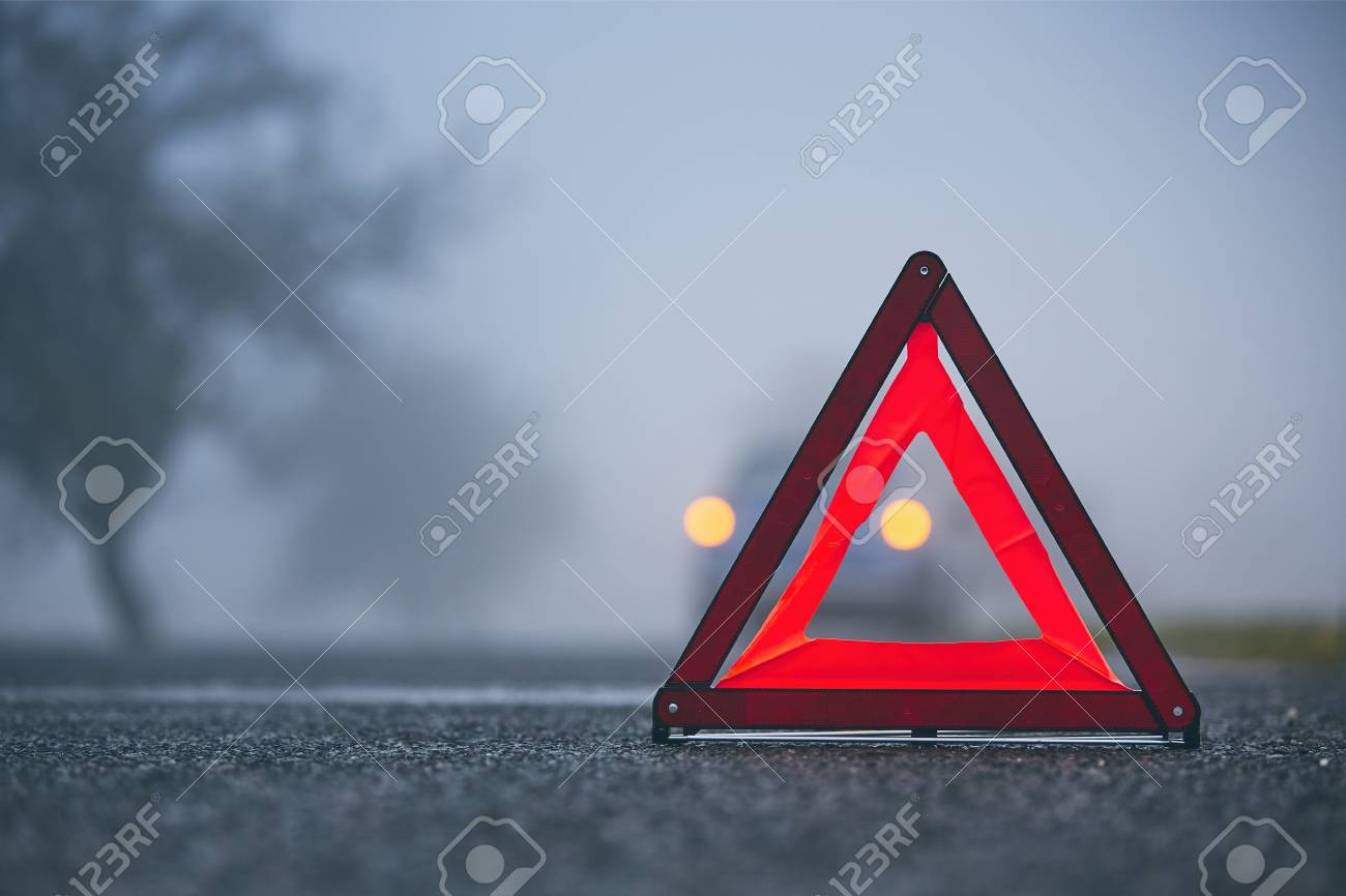 Traffic problem in thick fog. Car on the road behind warning triangle. - 111479370