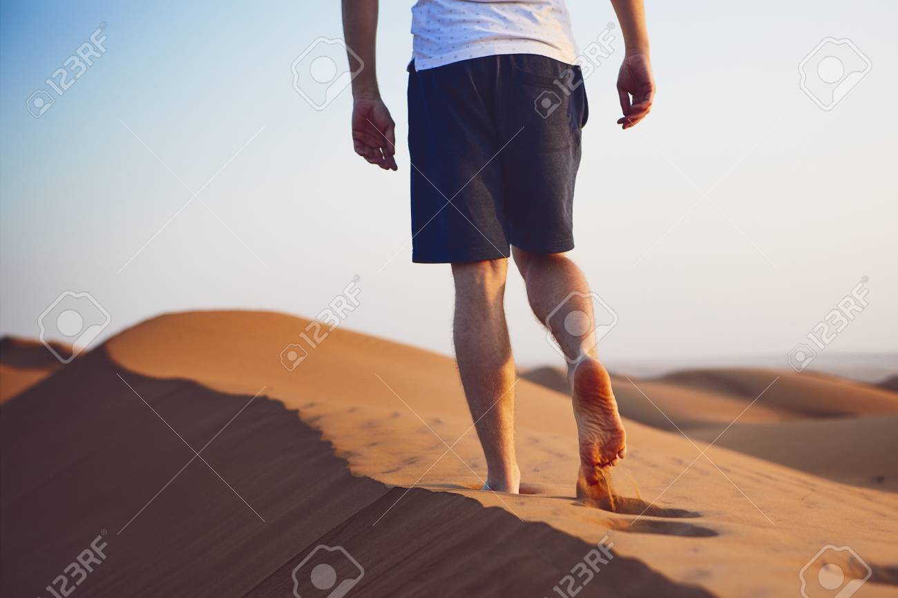 Young man walking on top of sand dune. Wahiba Sands in Oman. - 113363458