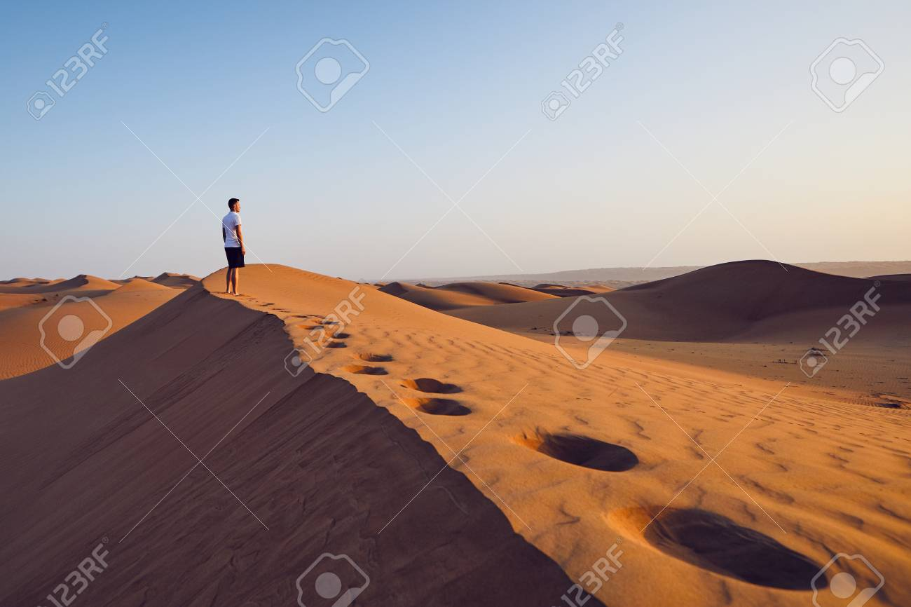 Young man standing on top of sand dune and looking at view. Desert Wahiba Sands in Oman. - 113363471