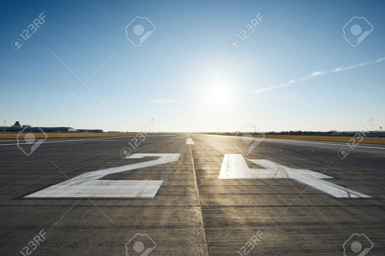 Surface level of airport runway with road marking and number 24 against clear sky. - 119803494