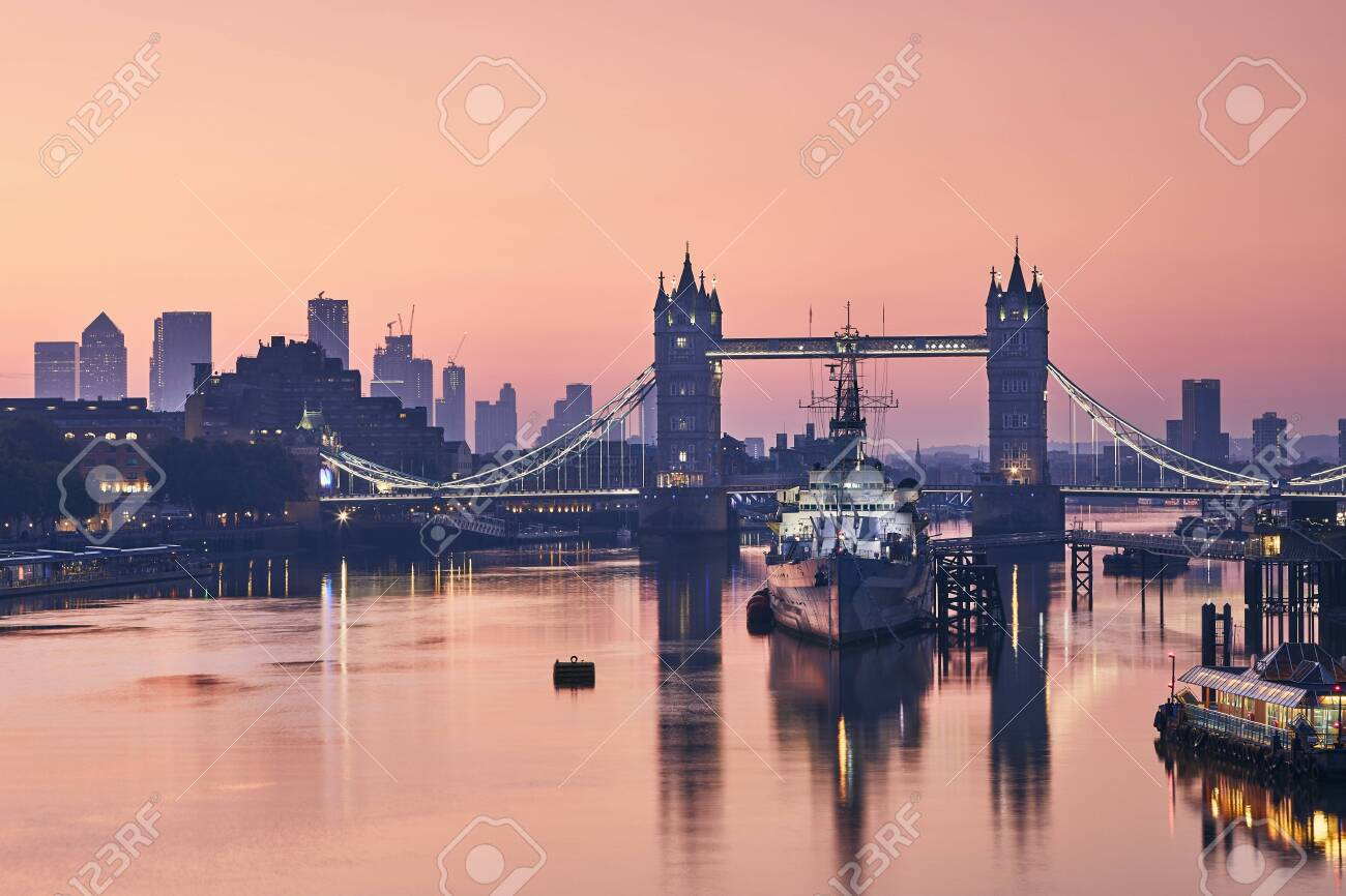 Skyline of London. Tower Bridge against cityscape with skyscrapes at dawn. - 129897036