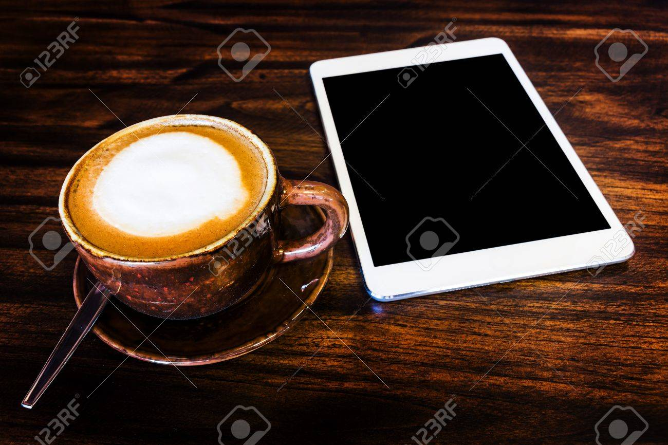 digital tablet and coffee cup on wooden table Stock Photo - 21061125