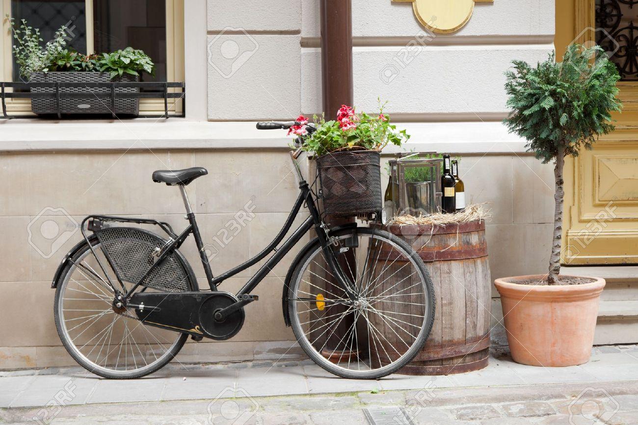 Deco Tonneau De Vin vieux vélo portant des fleurs comme décoration, tonneau en bois avec des  bouteilles de vin et des arbres en pot de fleurs
