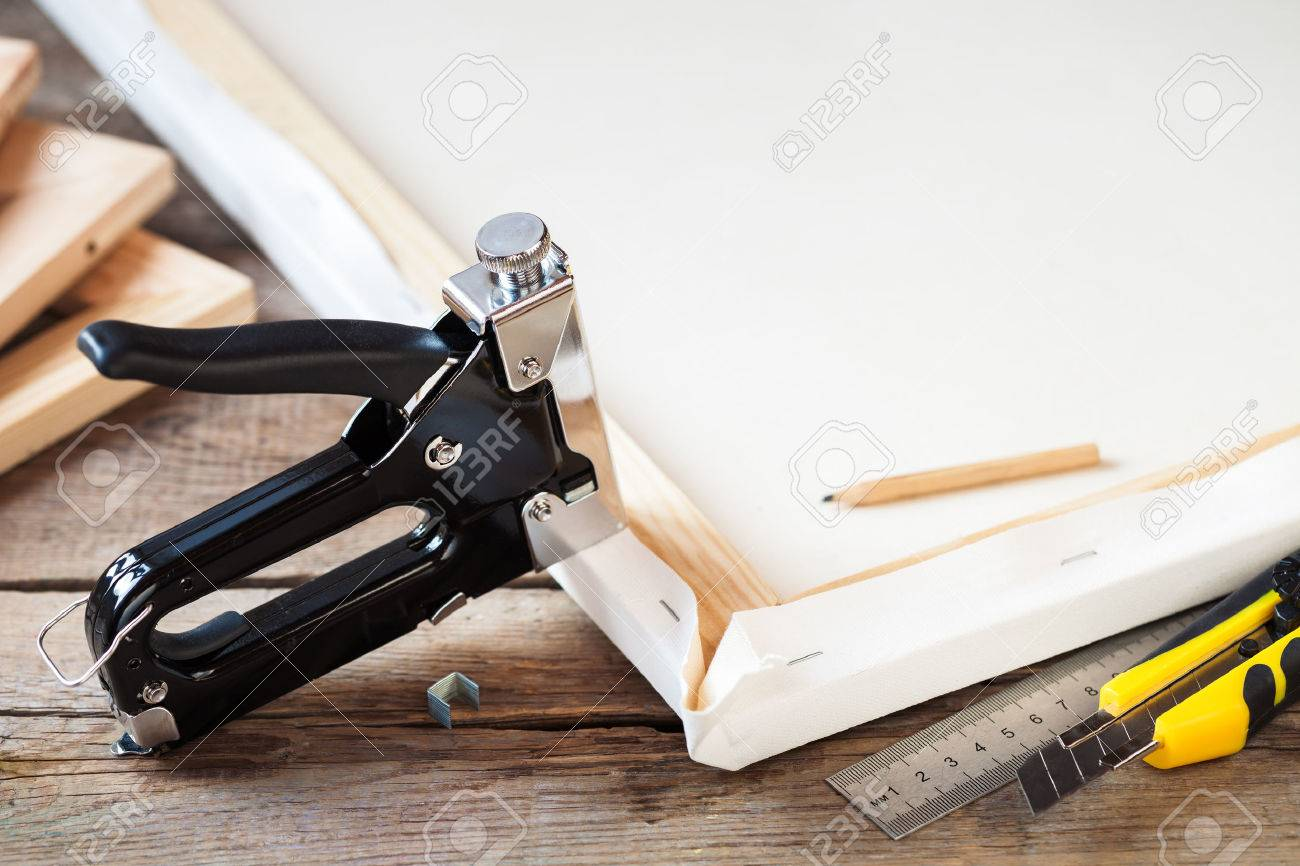 Artist canvas, canvas stretcher and staple gun on table - 51787023