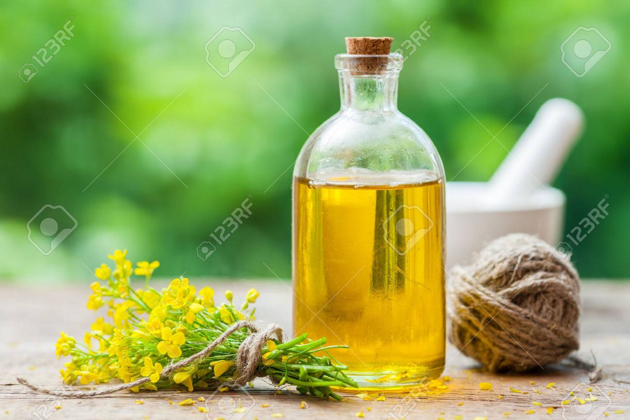 Bottle of rapeseed oil (canola) and repe flowers on table outdoors - 61088854