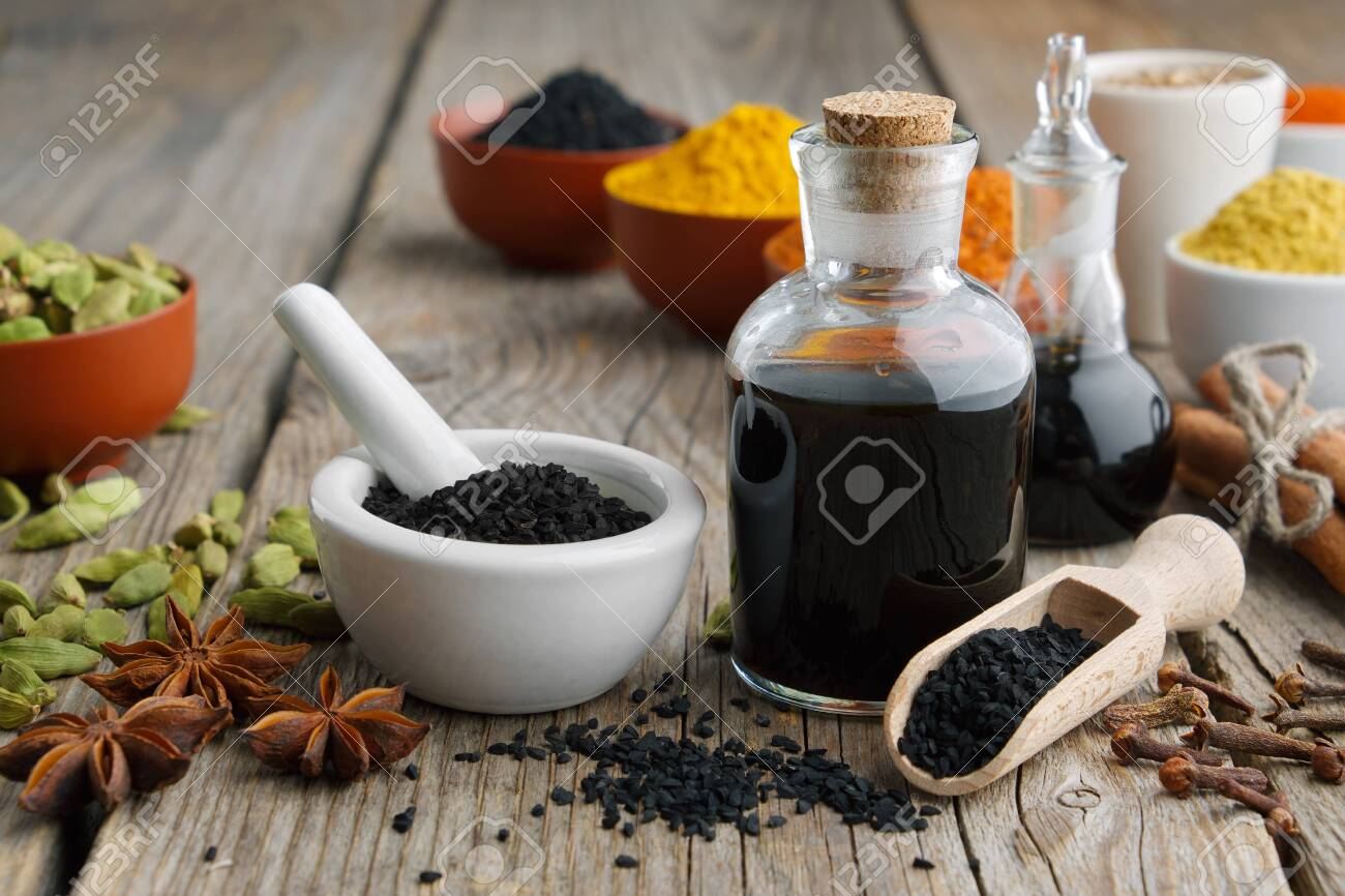 Black cumin or roman coriander seeds, black caraway oil bottles and aromatic spices and herbs - 140079774