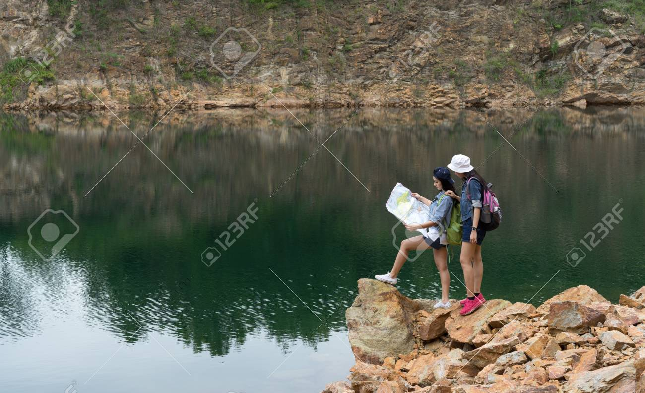 1d6c40f4420c Stock Photo - Young girl asian together with backpack standing on big rock  open maps location travel trip adventure in the mountain and lake
