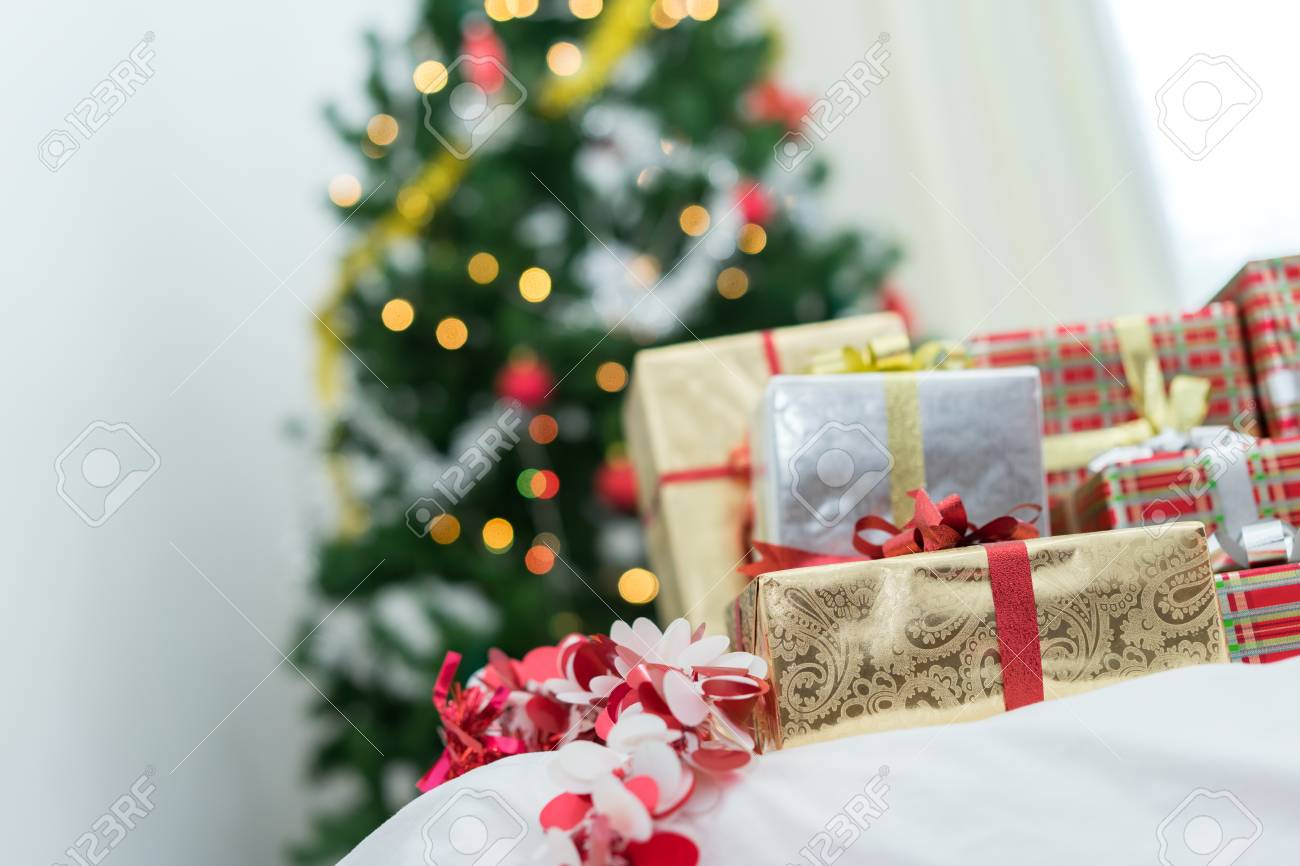At Home Christmas Trees.Many Gift Box Surprise Luxury On Bed And Christmas Tree Background