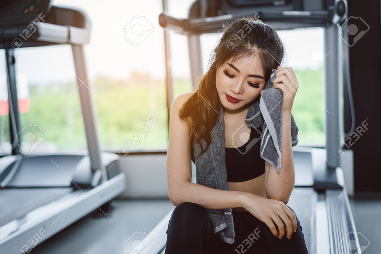 4bd9443e467 Stock Photo - Young asian woman athlete with handkerchief relax after break  workout and cardio sport exercise at fitness gym on treadmill for healthy  ...