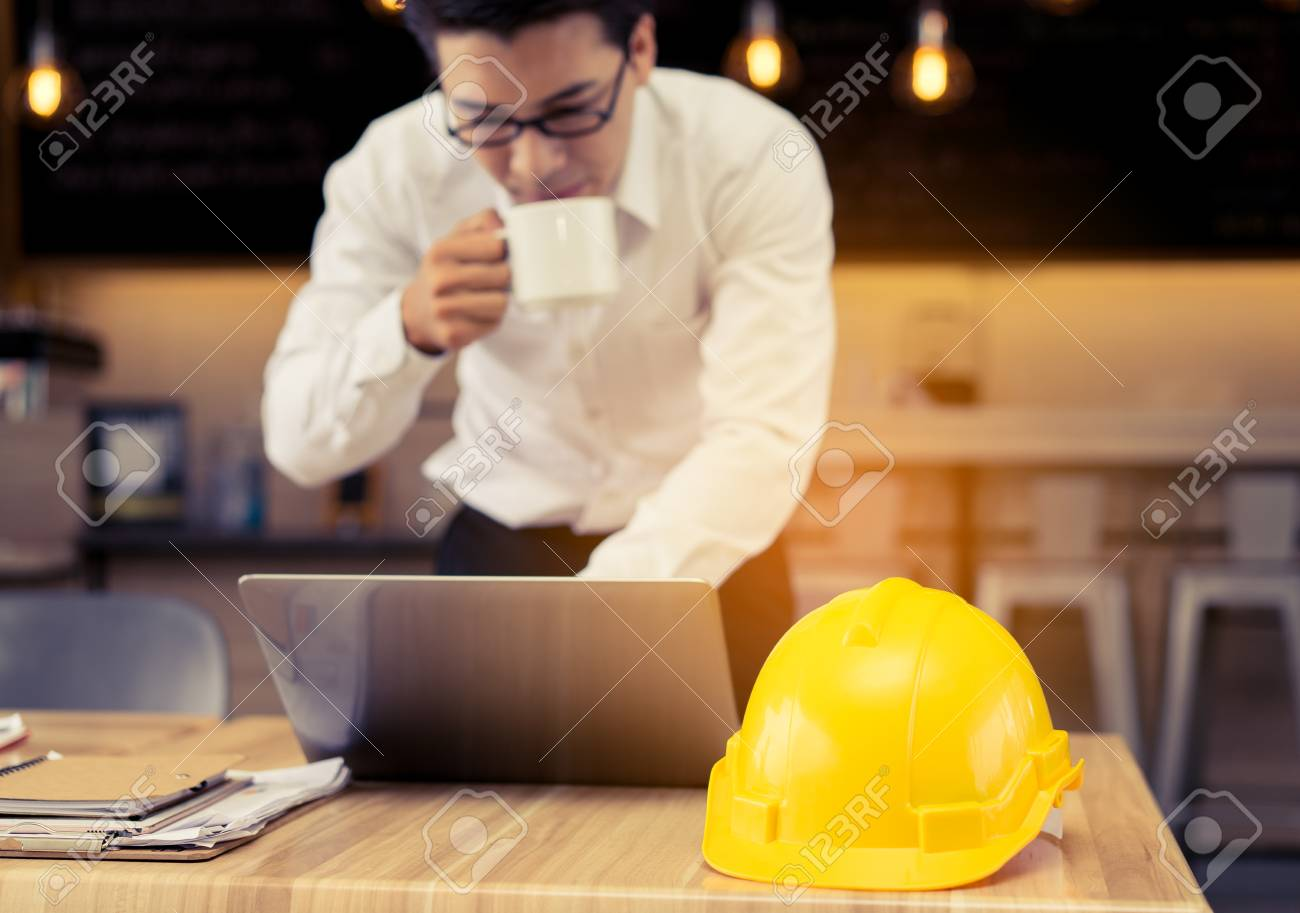 Engineer working business at office table with blueprintpaper engineer working business at office table with blueprintpaper plandocumentcalculator drinking malvernweather Image collections