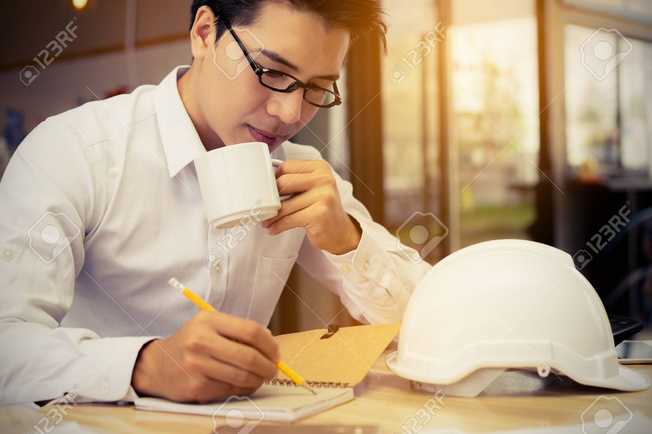Engineer working business at office table with blueprintpaper engineer working business at office table with blueprintpaper plandocumentcalculator drinking malvernweather Gallery