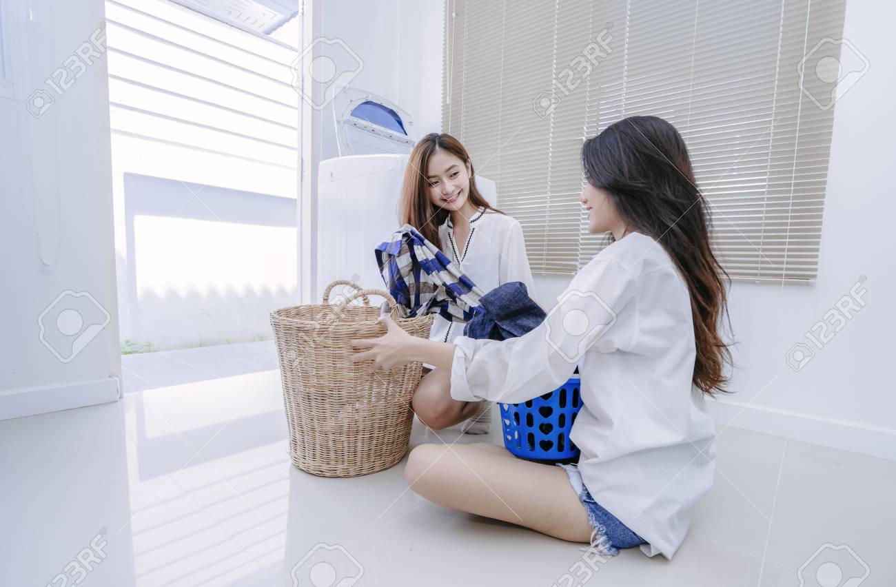 Same sex couple women asian doing housework or chores helping with washing  machine laundry loading clothes
