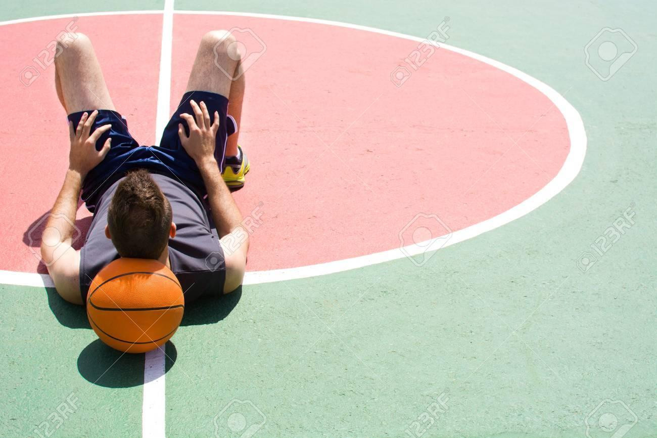 Sol Terrain De Basket homme allongé sur le sol d'un terrain de basket-ball