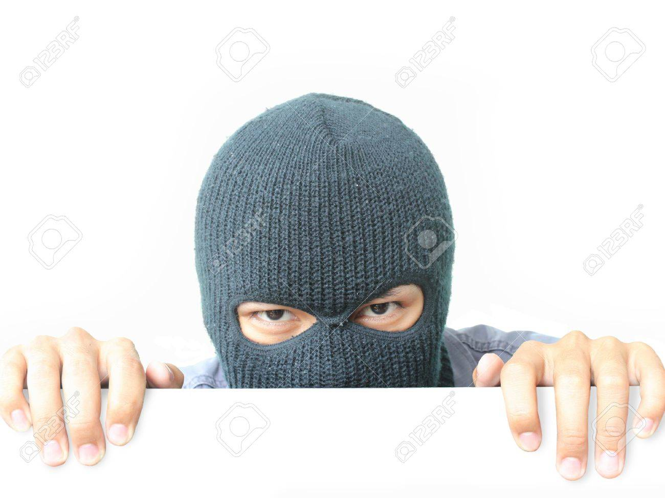 Robber hiding under a white wall Stock Photo - 10326431