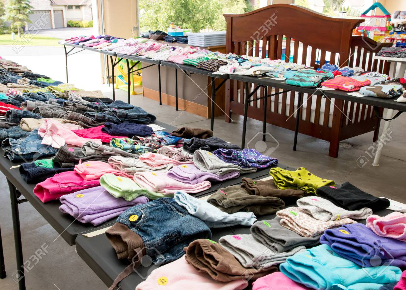 Tables of clothing and baby goods at suburban garage sale - 85058108