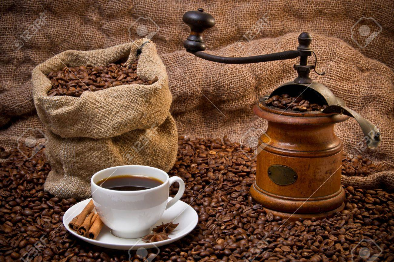 Sack of coffee beans, white cup and coffee-grinder still life. Scattered coffee beans - 8971609