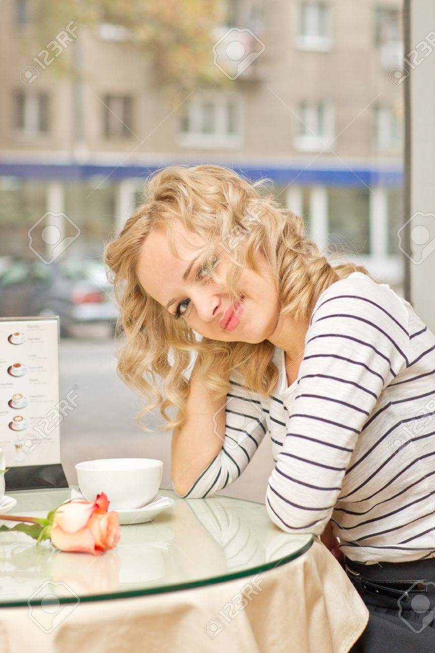 Attractive young blond woman smiles at small cafe Stock Photo - 16932719