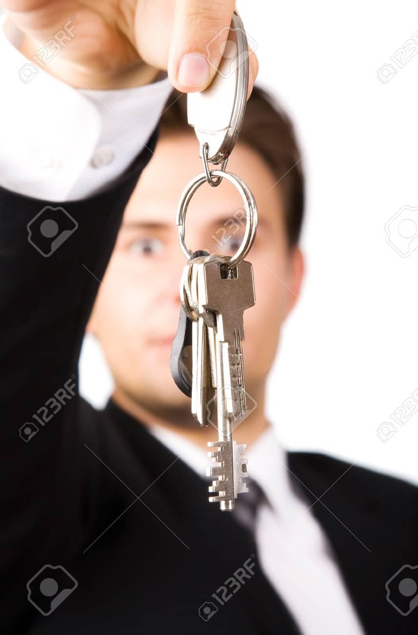 Young businessman holding keys. On white. Stock Photo - 5088976