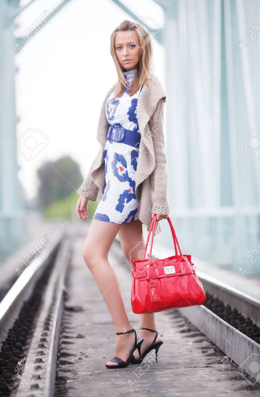 Young slim woman at the railway. Soft bright colors. Stock Photo - 5736190