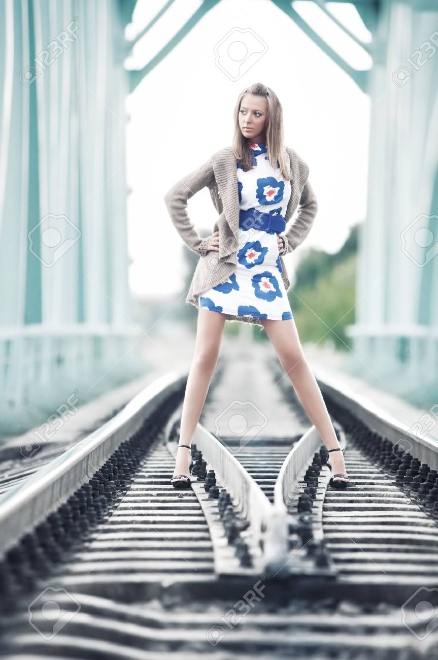 Young slim woman at the railway. Soft blue tint. Stock Photo - 5736162