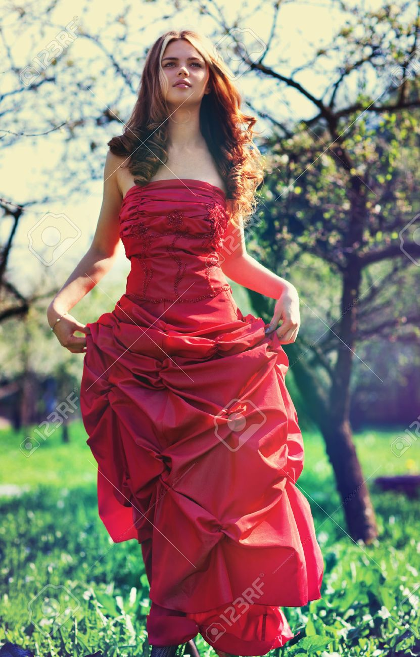 Young Woman In Red Dress In Garden. Film Style Colors. Stock Photo ...