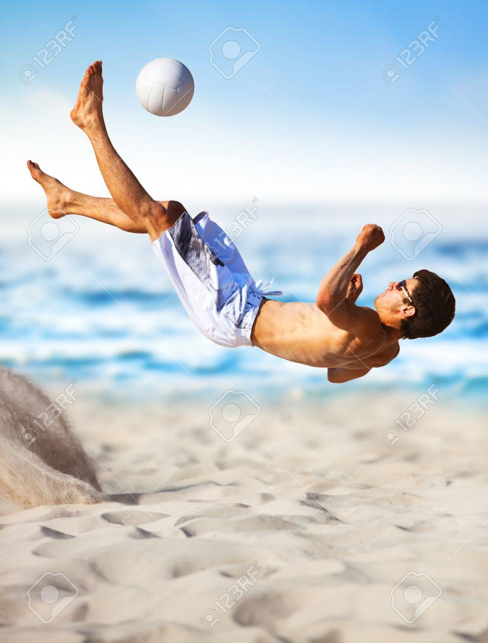 Young man playing soccer on beach. - 7442743