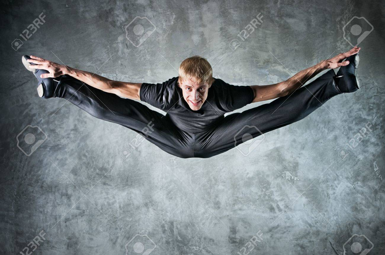 Young man dancer jumping up high. On wall background. Stock Photo - 7967861