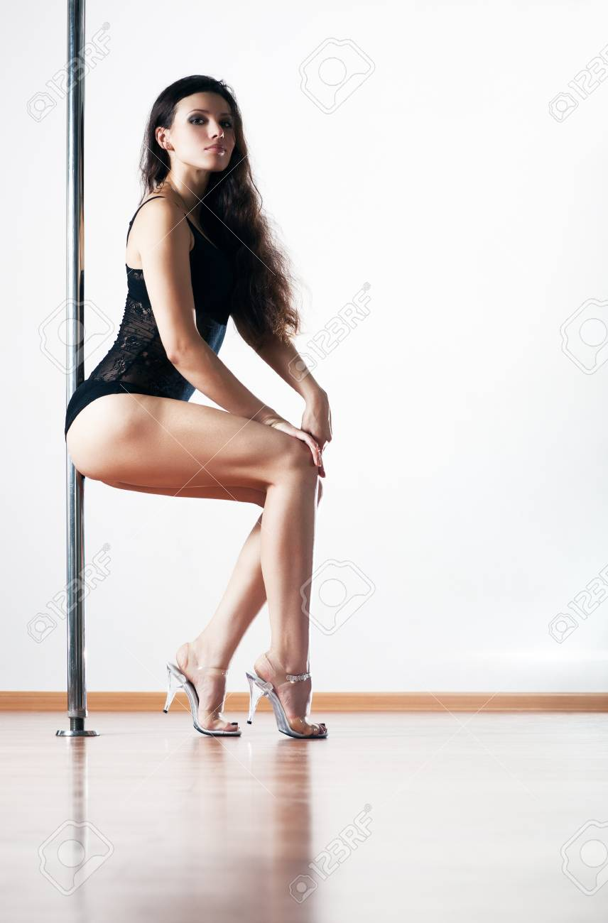 Young sexy pole dance woman. On white wall background. Stock Photo - 8509261