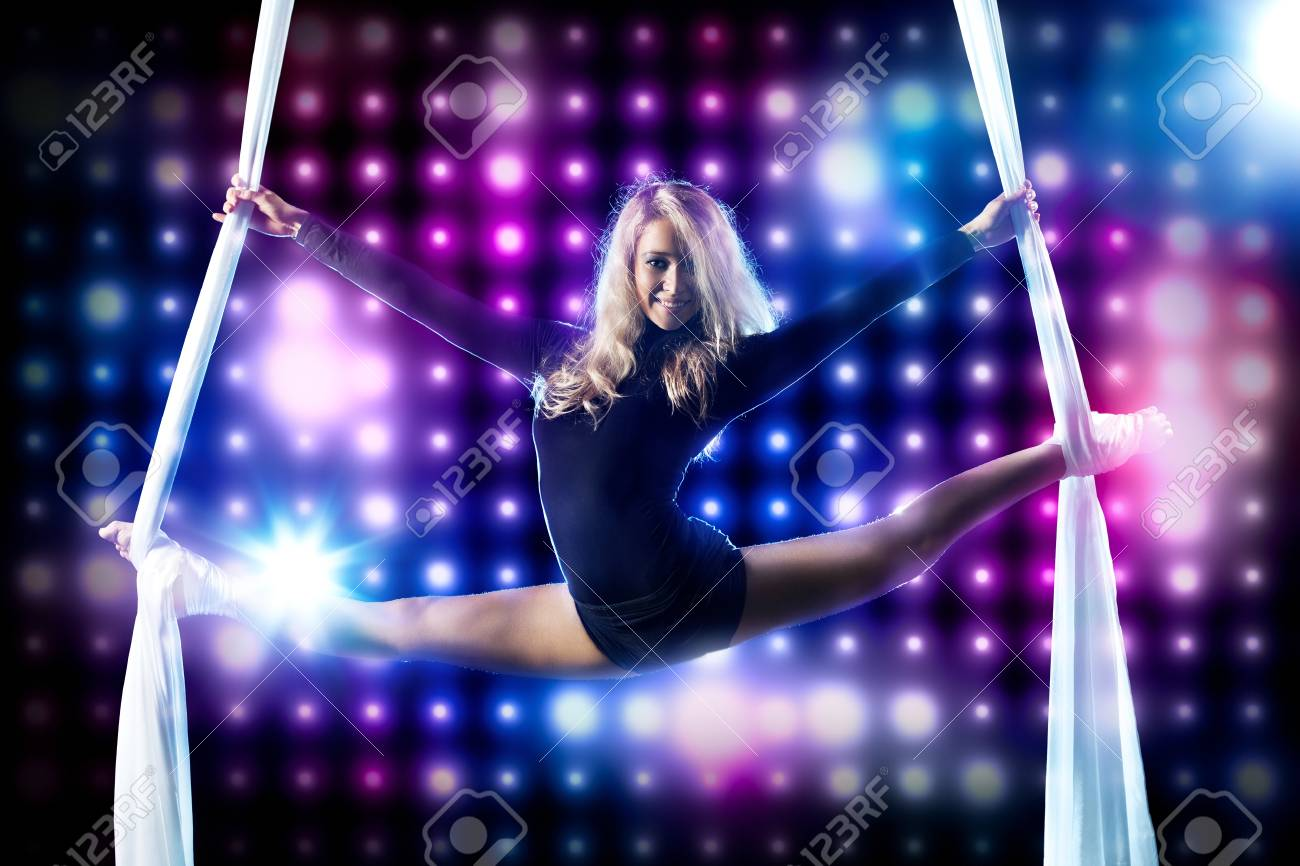 Young woman gymnast. On black background with lights. Stock Photo - 9405681