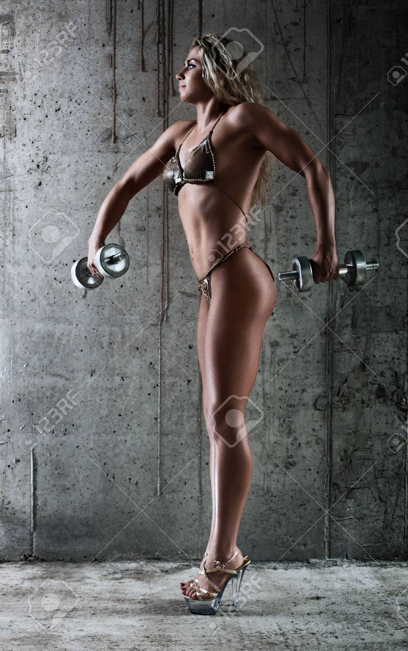 Young sexy muscular woman with dumbbell. Stock Photo - 11744414