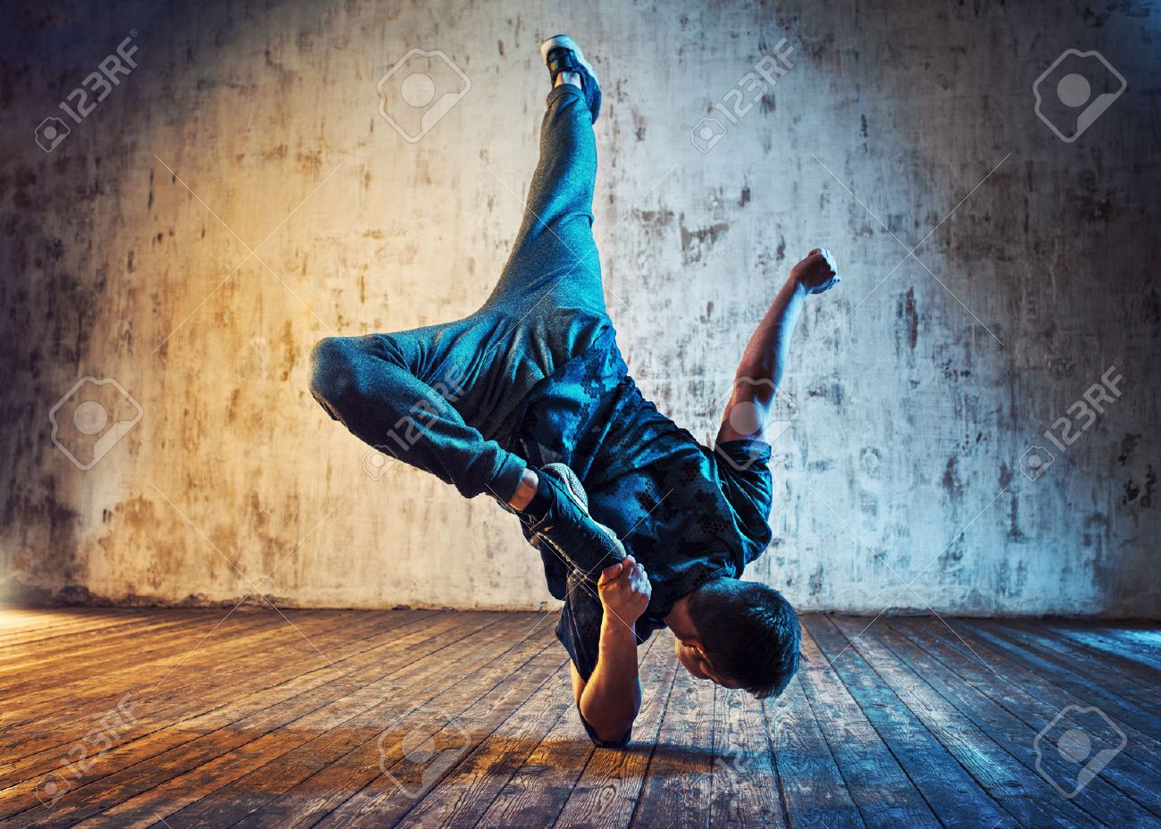 Young man break dancing on wall background  Blue and red lights