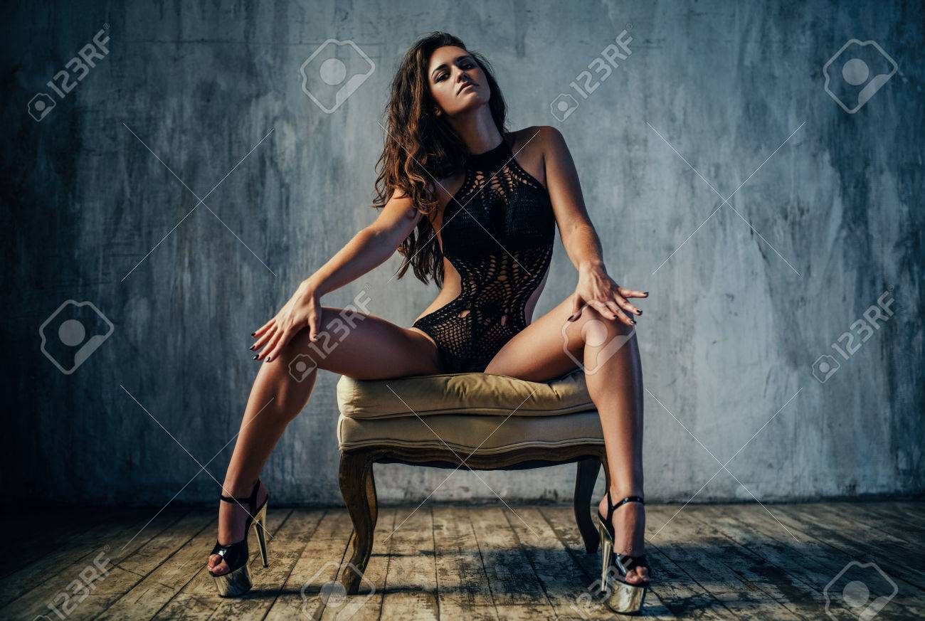 d9b5f50826c Stock Photo - Young sexy woman in black lingerie sitting on chair. Retro  style film colors effect.