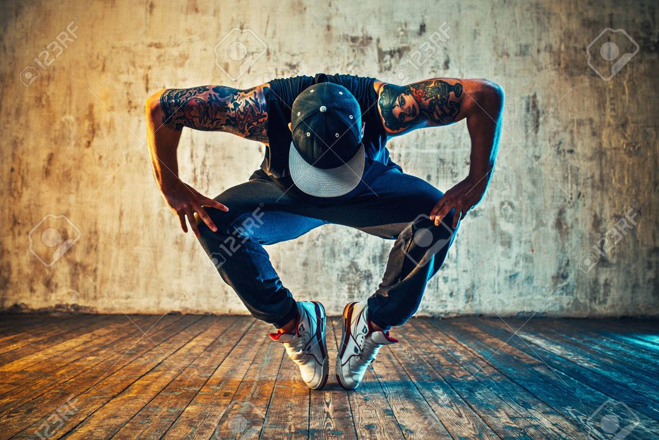 Young man break dancing on wall background. Blue and yellow colors tint. Tattoo on body. - 63355278