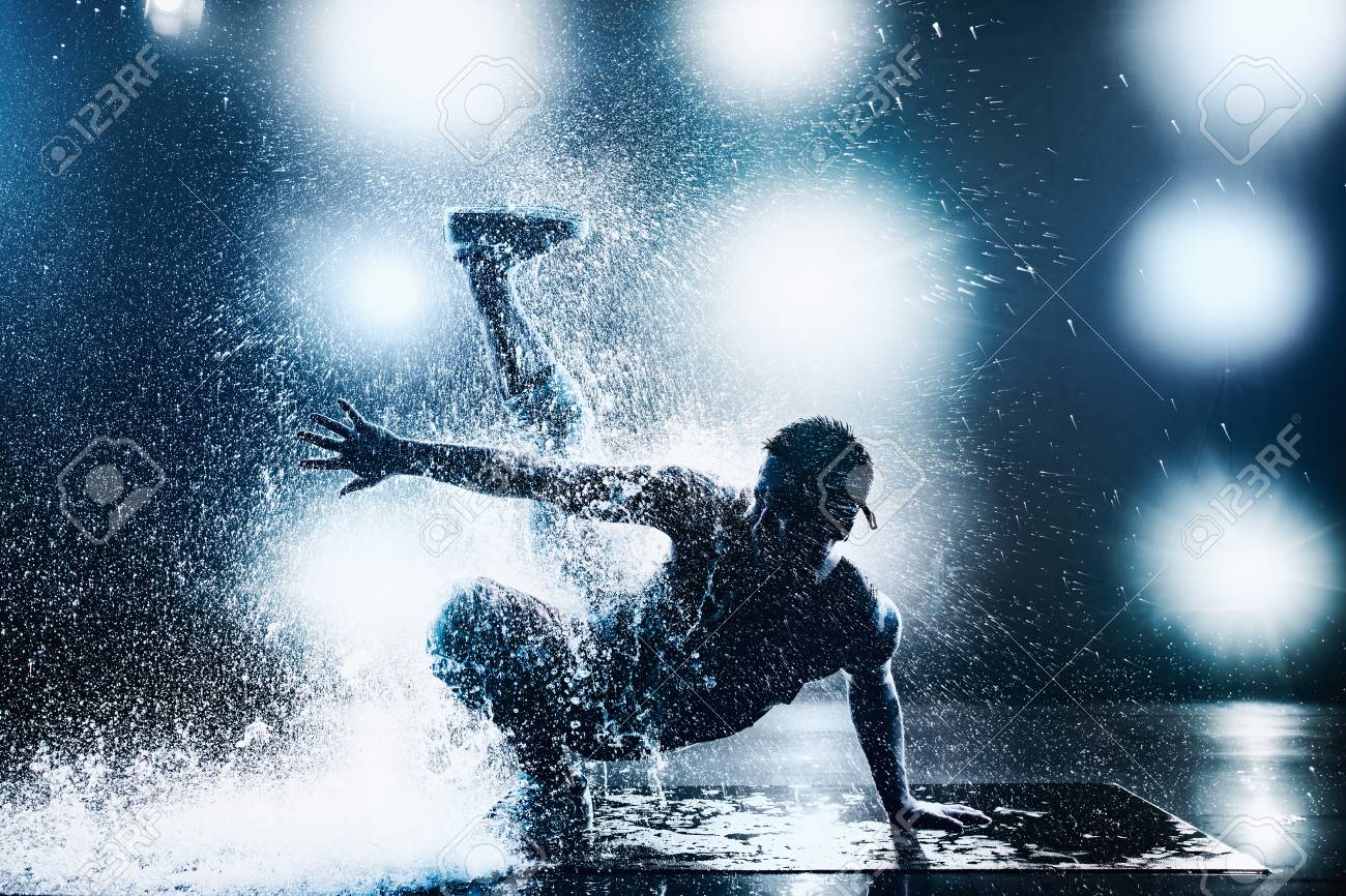 Young man break dancing in club with lights and water. Tattoo on body. Blue tint colors. - 91247253