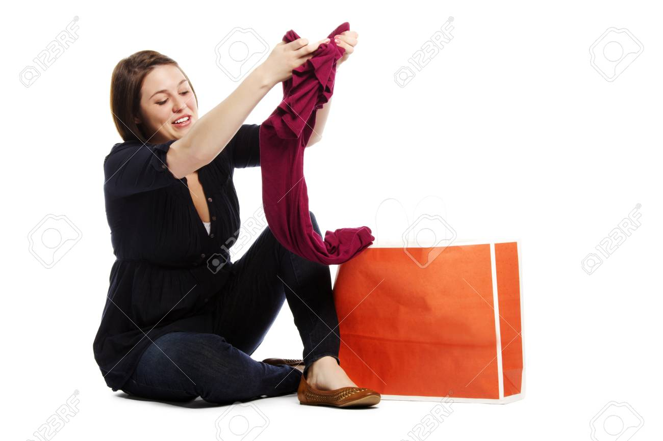 Portrait of an attractive young girl checking her new top from shopping bag on white background Stock Photo - 12833034