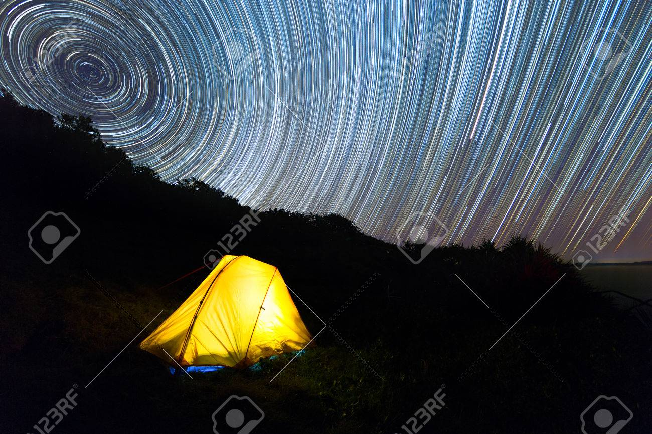 A Yellow Hiking Tent Illuminated With Light Under A Beautiful Night Sky Star  Trail. Stock
