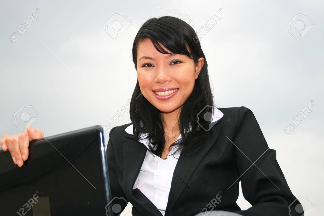Asian business woman outdoors on a laptop. Stock Photo - 8490718
